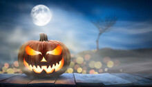 One Spooky Halloween Pumpkin, Jack O Lantern, With An Evil Face And Eyes On A Wooden Bench, Table With A Misty Night Full Moon Background With Space For Product Placement.