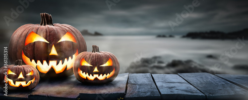 Photo Three spooky halloween pumpkins, Jack O Lantern, with an evil face and eyes on a wooden bench, table with a misty gray coastal night background with space for product placement