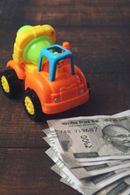 Plastic Toy Cement Mixer Truck With Indian Currency On Wooden Table - Vehicle Loan Concept