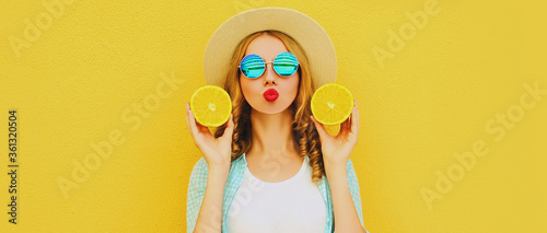 Fotografie, Obraz Summer portrait of young woman with fruits slice of orange blowing red lips send