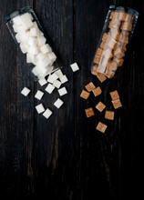 Top View Of White And Brown Sugar Cubes Scattered From Glass Jars On Dark Wooden Background With Copy Space