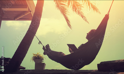 Fotografie, Obraz Woman an using a digital tablet  while relaxing in a hammock on a sand tropical