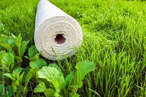 A roll of white geotextile lies on the green grass outside Fototapeta