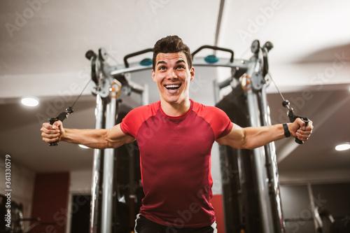 Fototapeta Young handsome man doing exercises in gym obraz