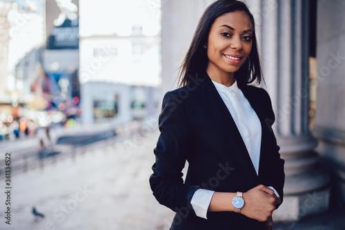 Fototapeta Successful black lady adjusting jacket in modern street obraz