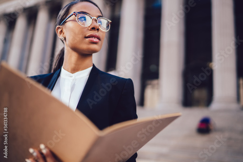 Thoughtful African American businesswoman in optical spectacles holding documents looking away while standing in urban setting with copy space Canvas Print