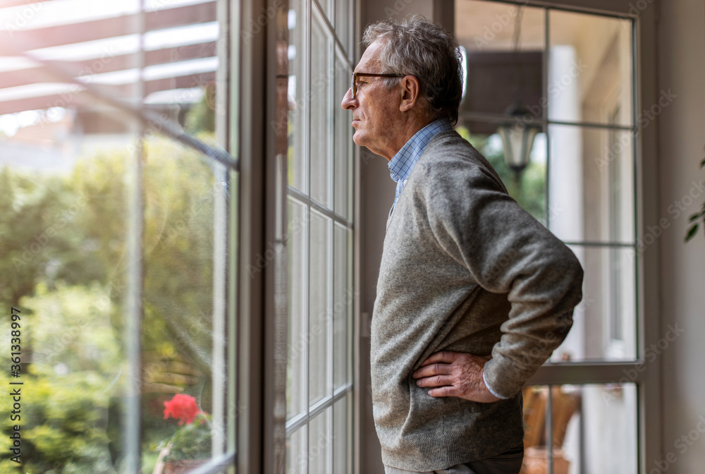 Fototapeta Senior man looking out of window at home
