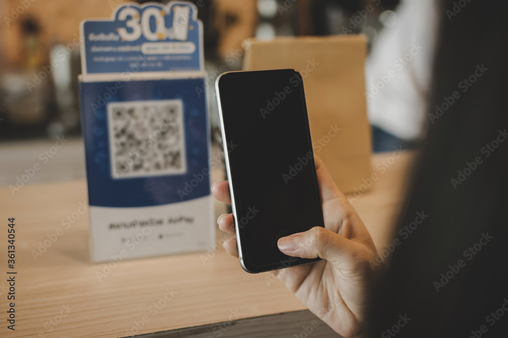 Fototapeta hand customer using digital mobile phone scan QR code paying for buying coffee in modern cafe coffee shop, cafe restaurant, digital payment, online shopping, takeaway food, internet technology concept