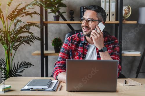 Fototapeta Portrait of smiling grey hair man with beard sitting front table with laptop, talking on phone obraz na płótnie