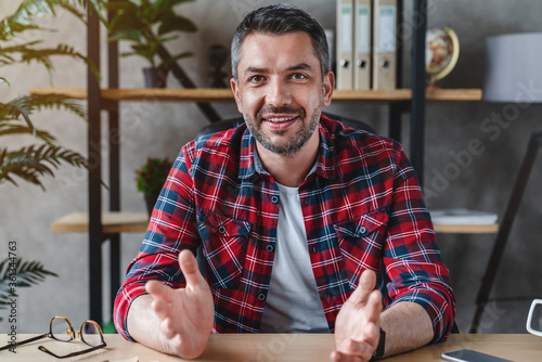 Obraz Middle aged man with gray hair looks at the camera speaks with his partner sitting at table in the office at home - fototapety do salonu