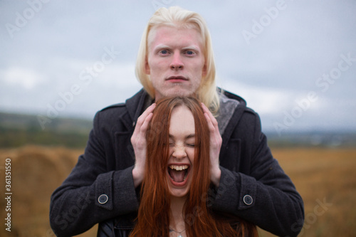 A handsome male albino model with an emotionless face in a black jacket holds his hands on the sides of a red-haired girl who screams against a wheat field Fototapet