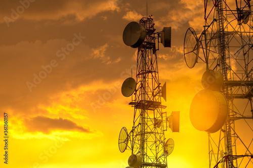 Fotografía Telecommunication towers with wireless antennas on golden sky
