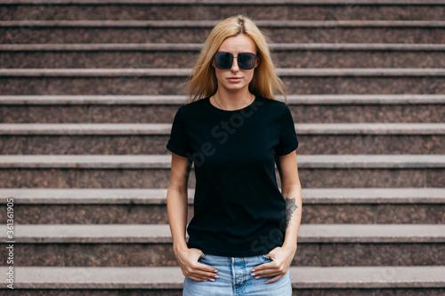 Fotografie, Obraz Stylish blonde girl wearing black t-shirt and glasses posing against street , urban clothing style