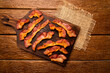 Leinwanddruck Bild - fried bacon strips on rustic wooden board