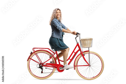 Fototapety, obrazy: Side shot of a young woman in a dress riding a red bicycle and looking at the camera