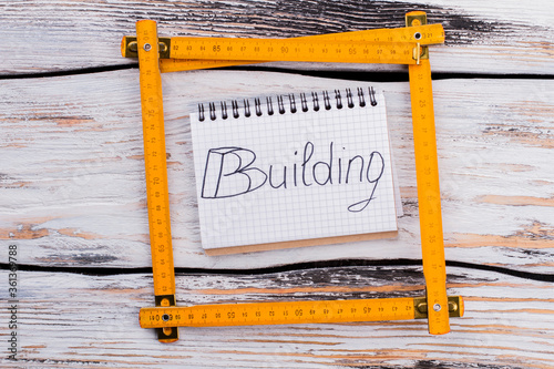 Fototapeta Yellow plastic carpenter ruler square on white wooden background. Top view flat lay. obraz