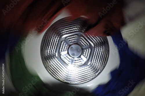 Motion blur view of moving clothing inside spinning laundry dryer. #361369934
