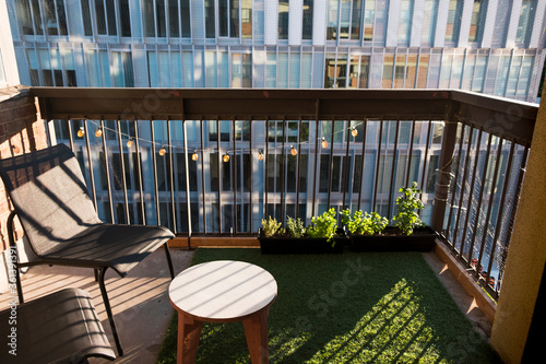 Fotografía Apartment balcony in city with grass turf and potted plants