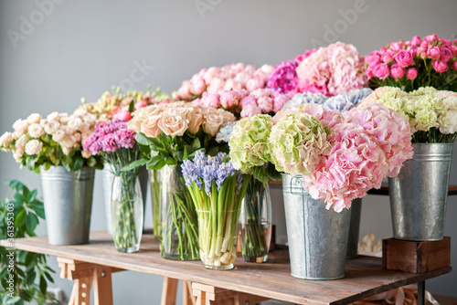 Many different colors on the stand or wooden table in the flower shop. Showcase. Background of mix of flowers. Beautiful flowers for catalog or online store. Floral shop and delivery concept. Top view