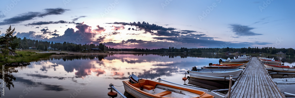 Fototapeta Sunrise during midnight light in Swedish Lapland, sea jetty, lot of parked boats, clouds reflection in crystal clear calm water. Sunrise starting, tourist attraction in Northern Sweden Umea, subpolar