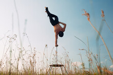 A Man Of Athletic Build Performs Complex Gymnastic Exercises In A Field At Sunset.