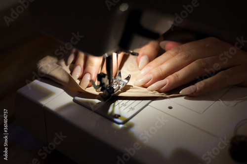 Photo The woman is sewing with sewing machine