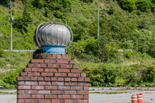Round Exhaust Vent On Top Of Red Brick Chimney.