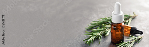 Bottles with rosemary essential oil on grey background, space for text. Banner design