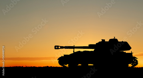 Obraz na plátne Silhouette of army tank at sunset outdoors. Military machinery