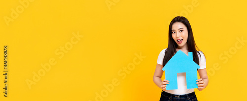 Obraz Young beautiful Asian woman holding new house model cutout isolated on colorful yellow banner background with copy space - fototapety do salonu