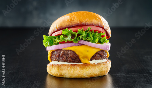 Fototapeta thick cheeseburger with american cheese, lettuce tomato and onion obraz