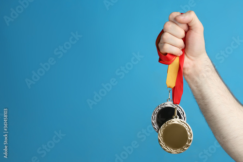 Fotografía Man holding medals on blue background, closeup. Space for design