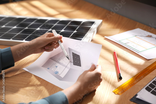 Fotomural Woman working on house project with solar panels at table in office, closeup