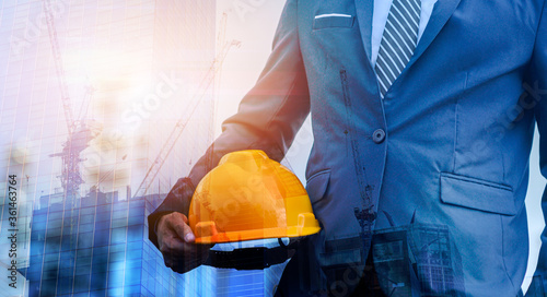 Double Exposure of building under construction and man engineer is holding helmet wearing a suit thinking of ways and ideas for building new buildings in the future Slika na platnu