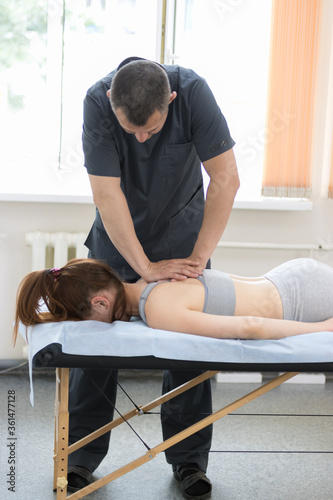 Young woman having osteopathy treatment - the master pushing on the back Fototapeta