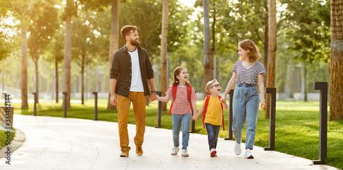 Happy family walking to school in park.