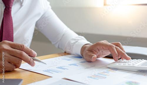 Fototapeta Asian business men calculate finances using graphs and calculators in the office. obraz