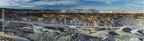 Panorama of the relief in a large stone quarry for the extraction of limestone with working in it of mining equipment Canvas Print