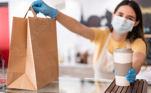 Young woman wearing face mask while serving takeaway breakfast and coffee inside cafeteria restaurant - Worker preparing delivery food inside bakery bar during coronavirus period - Focus on right hand - 361499927