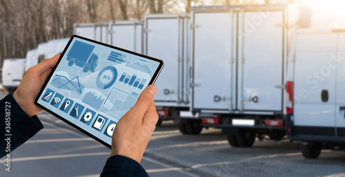 Manager with a digital tablet on the background of trucks Canvas Print