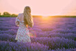 canvas print picture - Happy woman dancing in a lavender field at sunset. Beautiful flower meadow. Summer sunset colorful lighting