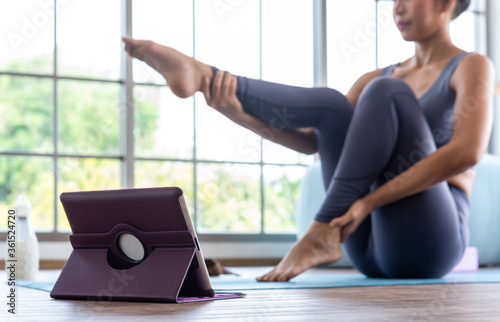 Asian woman practising yoga at home online use tablet attend online course Canvas Print