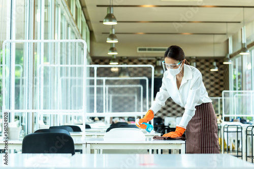 Obraz Woman restaurant staff cleaning table with alcohol spray wearing glove, face shield and mask before open the restaurant - fototapety do salonu