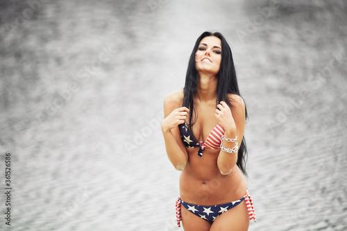 Fototapeta Woman on the beach in a bathing suit with an American flag having fun obraz na płótnie