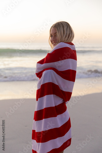 Caucasian woman covering herself with a US flag at the beach