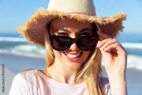 Woman wearing hat and sunglasses smiling