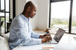 canvas print picture - Photo of african american man working with laptop while sitting at table