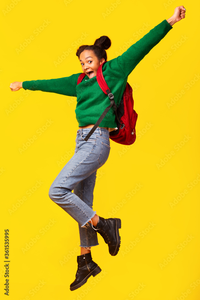 Fototapeta Excited afro girl jumping over yellow background