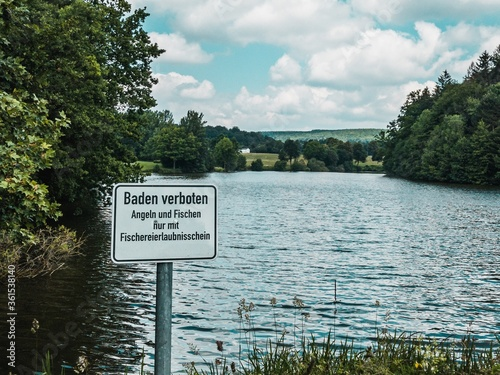 Sign saying 'swimming prohibited' and 'fishing only with appropriate approval' b Canvas Print