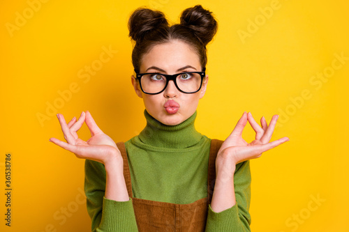 Portrait of childish crazy girl inflate cheeks make om sign meditate asana charka exercise wear green pullover isolated over bright shine color background - 361538786